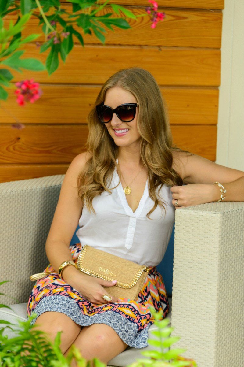 Ashley Nicholas from Ashley Brooke wearing Kendra Scott jewelry, Lilly Pulitzer clutch, Bella Dahl top, and Express sunglasses at the Gates Hotel Key West