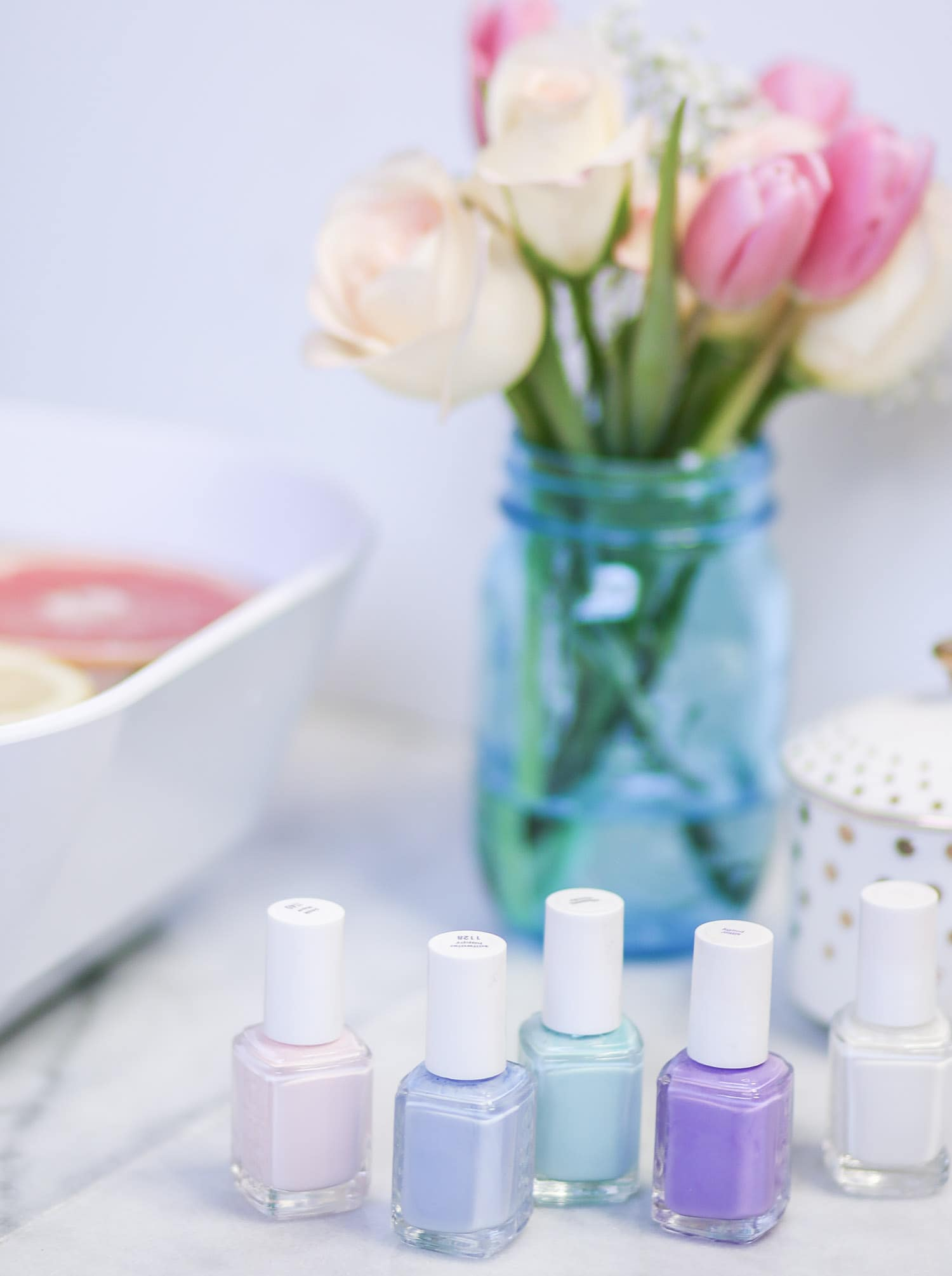 Learn how to create a luxurious DIY spa night at home. Ashley Brooke from ashleybrookenicholas.com is sharing her favorite DIY beauty treatment recipes, including a relaxing citrus and mint hand and foot soak. It's the perfect way to soften hands and feet before painting your nails with a pastel Essie nail polish!