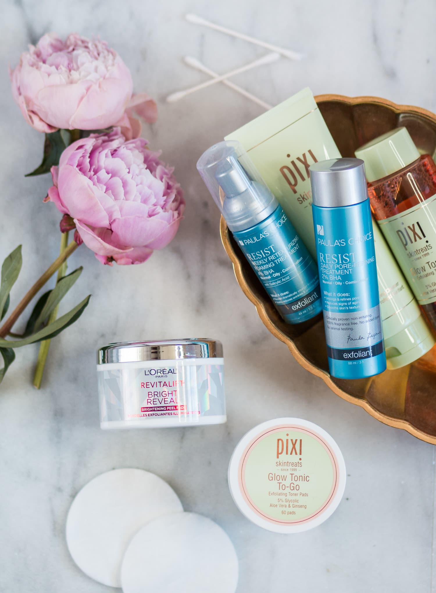 The best new skincare products for women in their 20s - including the best acid toners + a review of Paula's Choice Resist Daily Pore-Refining Treatment 2% BHA, Paula's Choice Resist Weekly Retexturizing Foaming Treatment 4% BHA, L'ORÉAL Revitalift Bright Reveal Peel Pads, and Pixi Beauty Glow Tonic To-Go Exfoliating Toner Pads by beauty blogger Ashley Brooke Nicholas