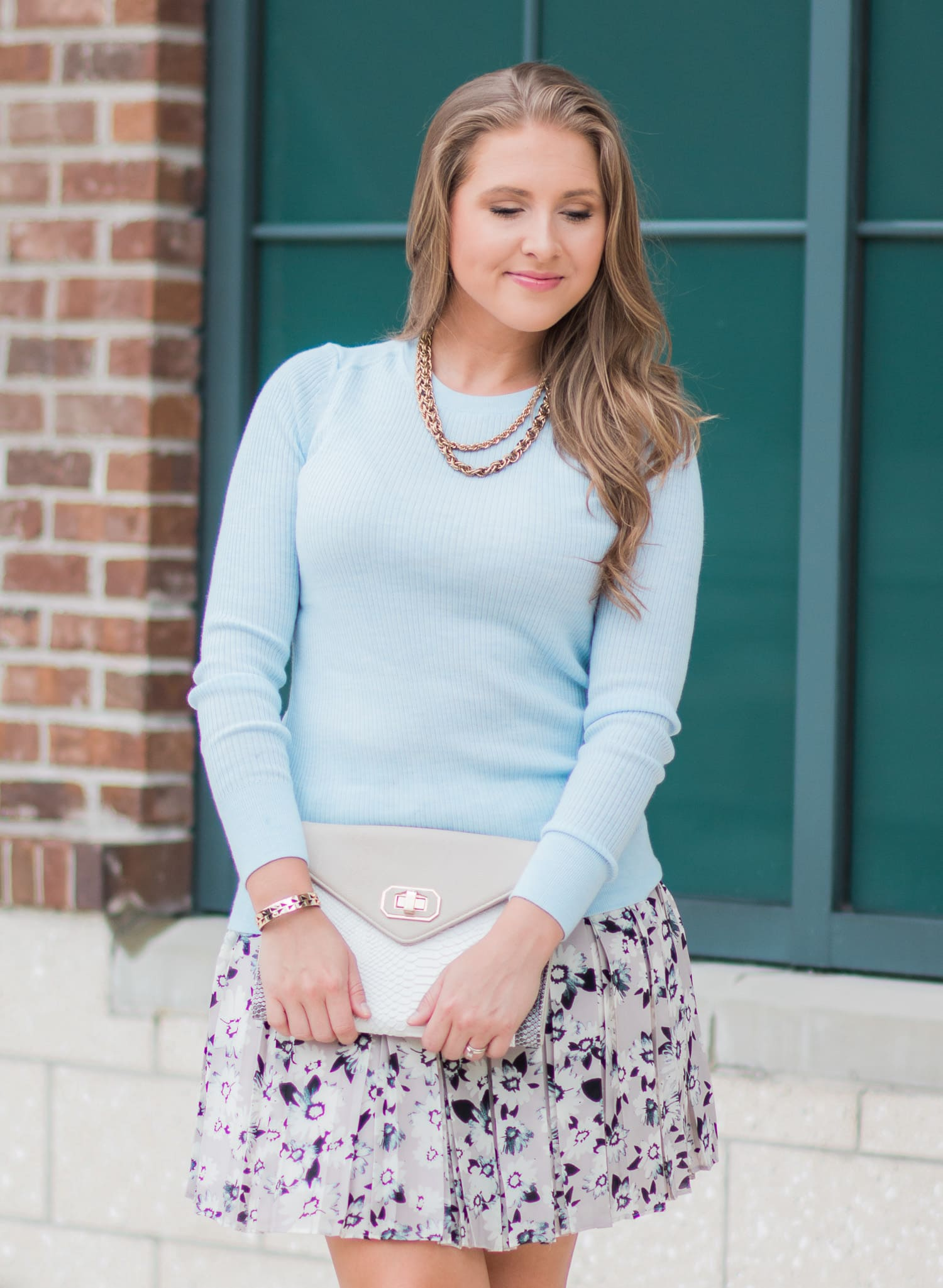 Banana Republic pleated floral skirt, ribbed baby blue sweater, and nude bow heels. Such a perfect transitional summer to fall outfit idea. Click through to see the full outfit from blogger Ashley Brooke Nicholas.