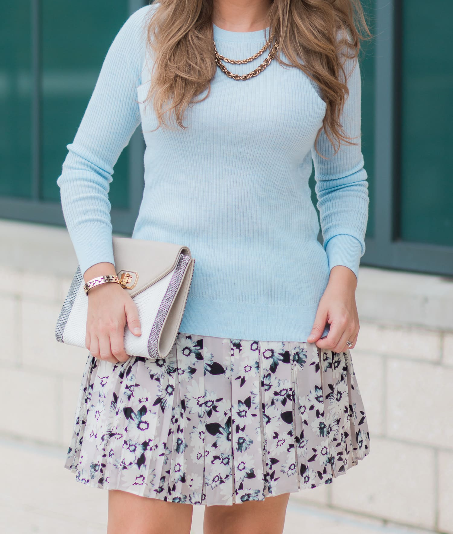 Banana Republic pleated floral skirt, ribbed baby blue sweater, nude clutch, Stella & Dot Addison cuff, gold chain necklace, and nude bow heels. Such a perfect transitional summer to fall outfit idea. Click through to see the full outfit from blogger Ashley Brooke Nicholas.