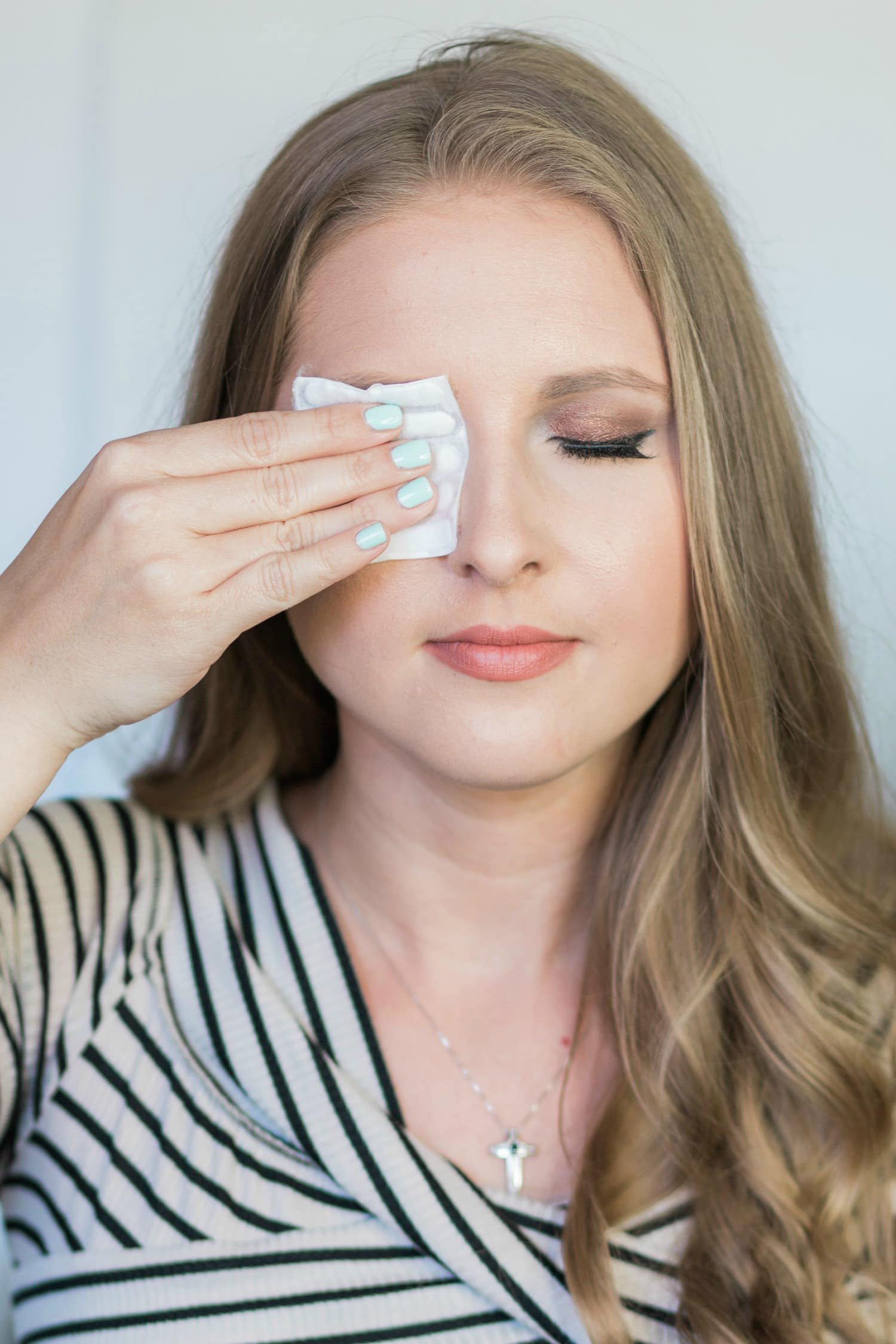 How to remove every last bit of your makeup - even waterproof makeup, waterproof mascara, and lash glue) without irritating your skin! | Click through this image to see the three best makeup removers on the makeup in this post by beauty blogger Ashley Brooke Nicholas.