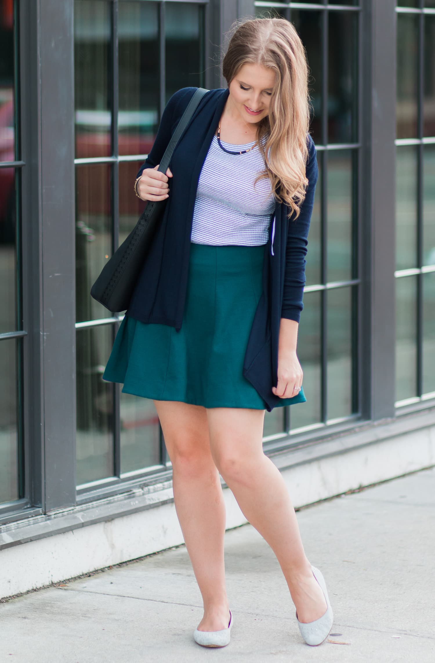 Casual fall outfit idea featuring Zara navy draped cardigan sweater, navy and white striped halter top, Urban Outfitters hunter green skater skirt, UGG grey ballet flats, Stella & Dot black leather and gold collar necklace, gold cuff bracelet, and black leather tassel hobo bag styled by fashion blogger Ashley Brooke Nicholas.