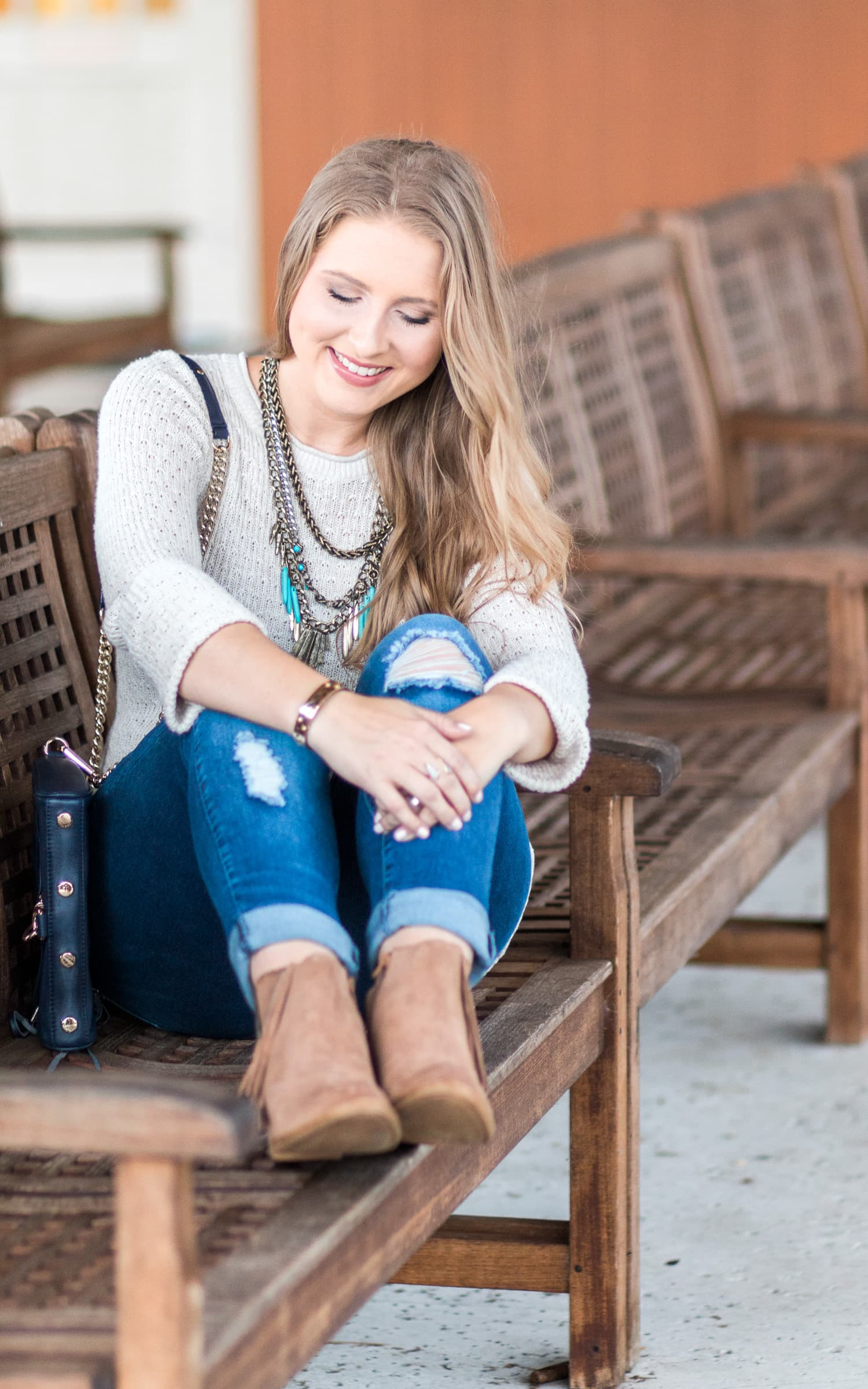 Cute fall outfit idea featuring a cream sweater with lace ruffle, destroyed denim jeans, navy crossbody bag, antiqued gold and turquoise statement necklace, and Lucky Brand Beeliner fringe booties styled by blogger Ashley Brooke Nicholas.