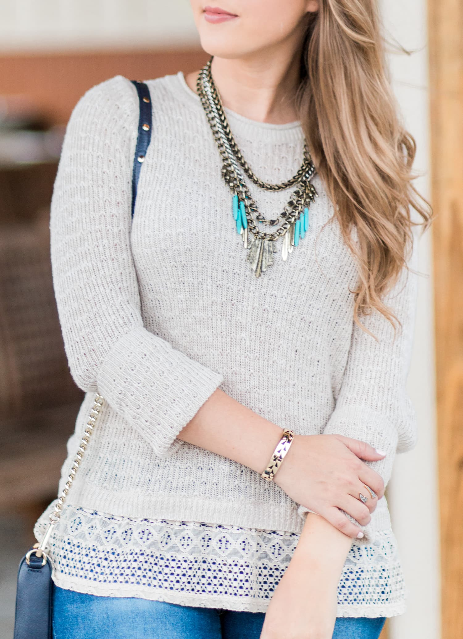 Cream sweater with lace ruffle, destroyed denim jeans, navy crossbody bag, and antiqued gold and turquoise statement necklace styled by blogger Ashley Brooke Nicholas. Click through this image to see this cute fall outfit idea + learn where to buy each item.