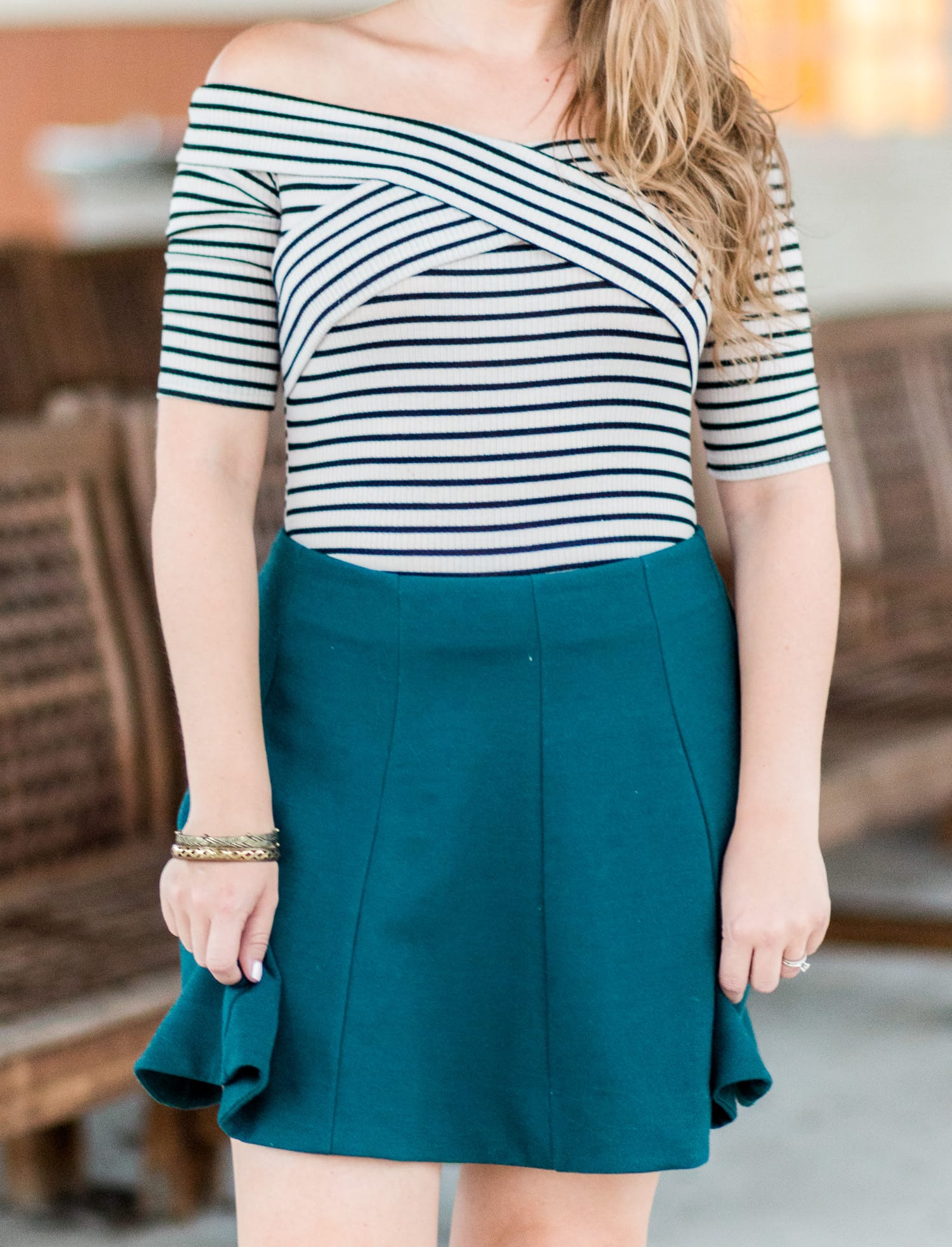 Striped off-the-shoulder top + hunter green skater skirt + distressed gold bracelets styled in a cute fall outfit idea by style blogger Ashley Brooke Nicholas