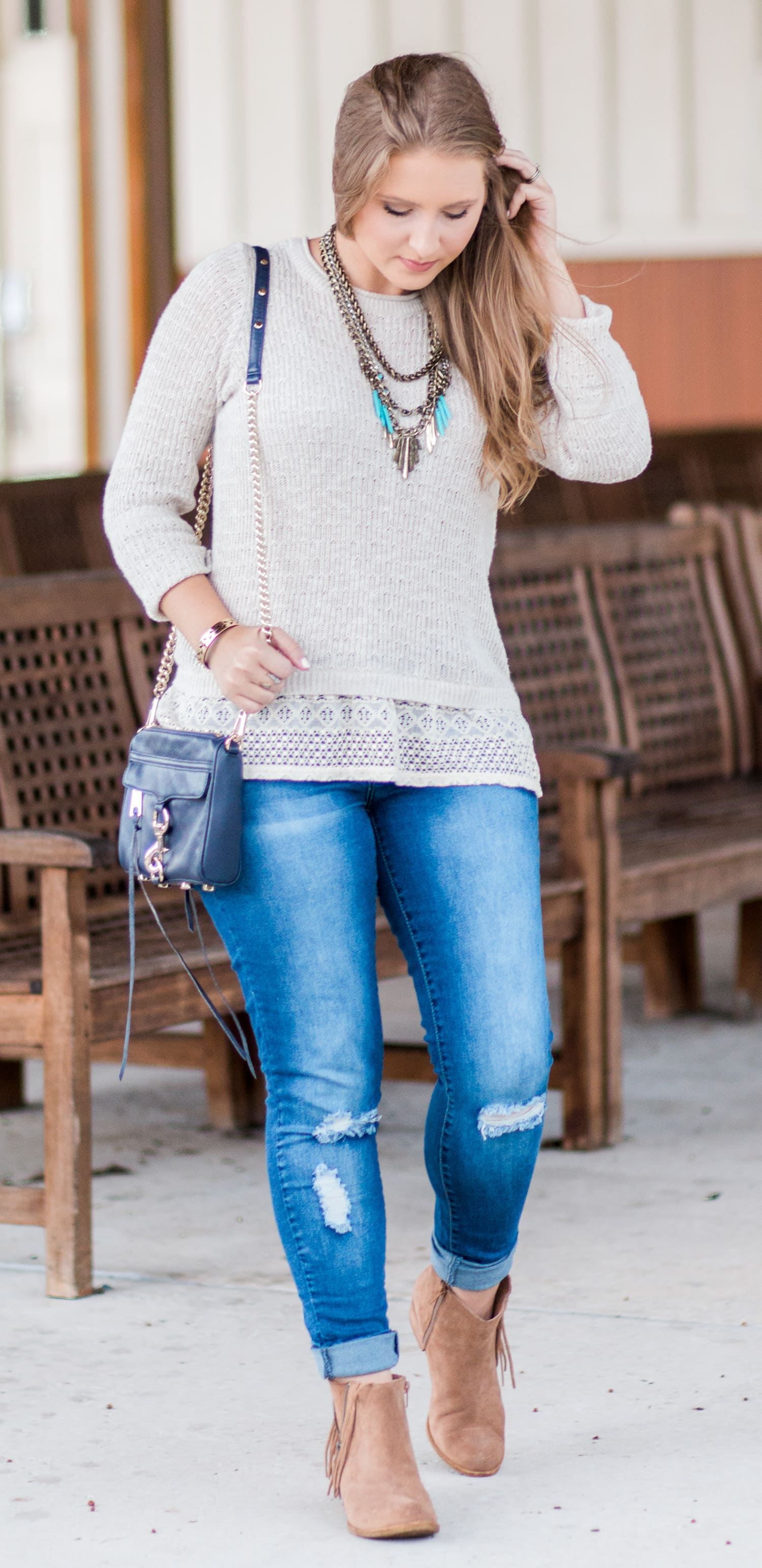 Cream sweater with lace ruffle, destroyed denim jeans, navy crossbody bag, antiqued gold and turquoise statement necklace, and Lucky Brand Beeliner fringe booties styled by blogger Ashley Brooke Nicholas. Click through this pin to see this cute fall outfit idea + learn where to buy each item.