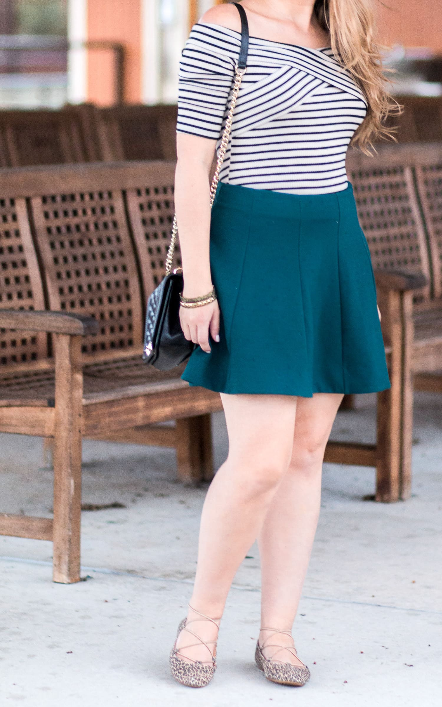 Rebecca Minkoff black and gold Love crossbody bag, antiqued gold bracelets, hunter green skater skirt, and Lucky Brand Aviee leopard print lace-up flats
