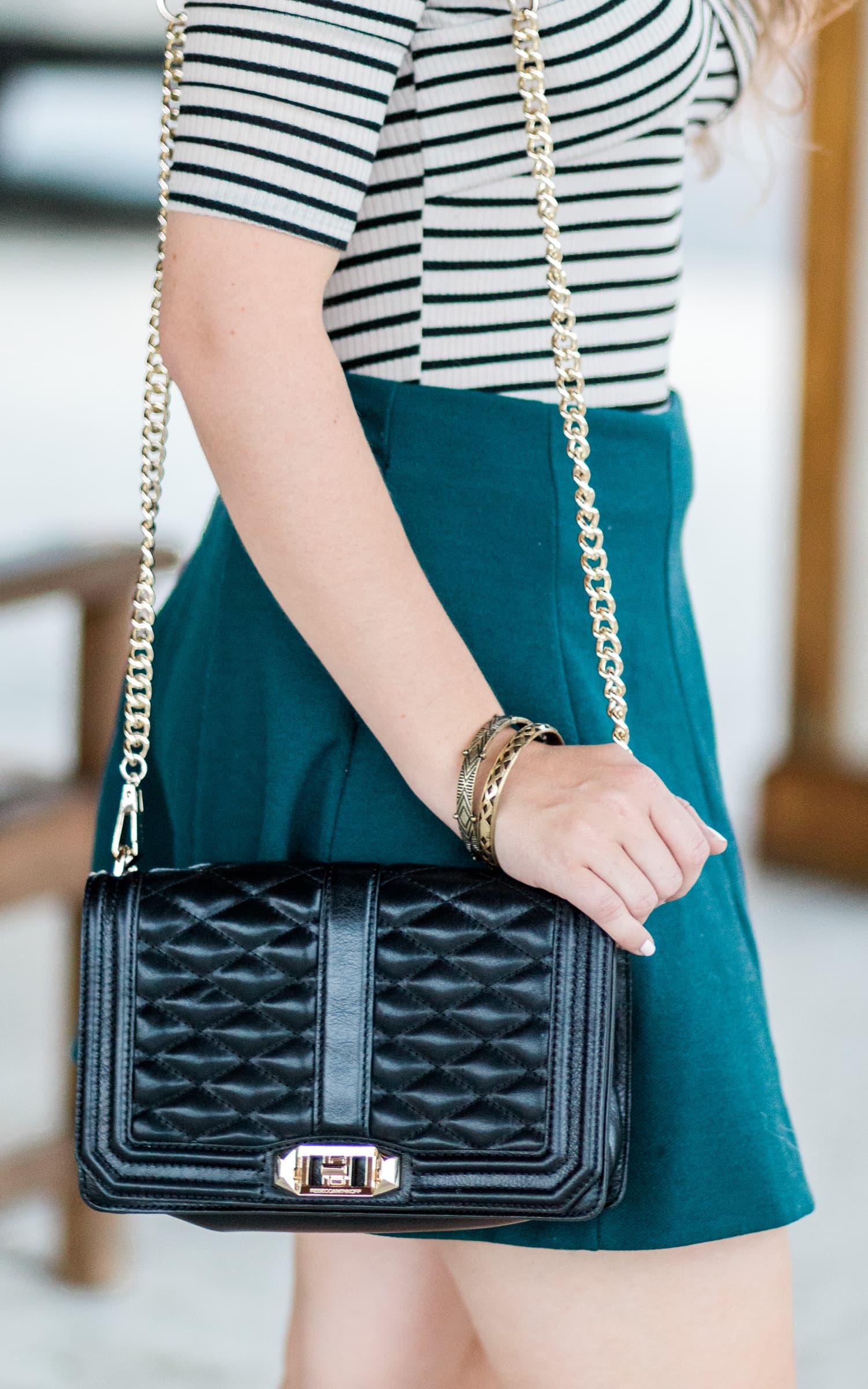 Rebecca Minkoff black and gold Love crossbody bag, antiqued gold bracelets, and a hunter green skater skirt