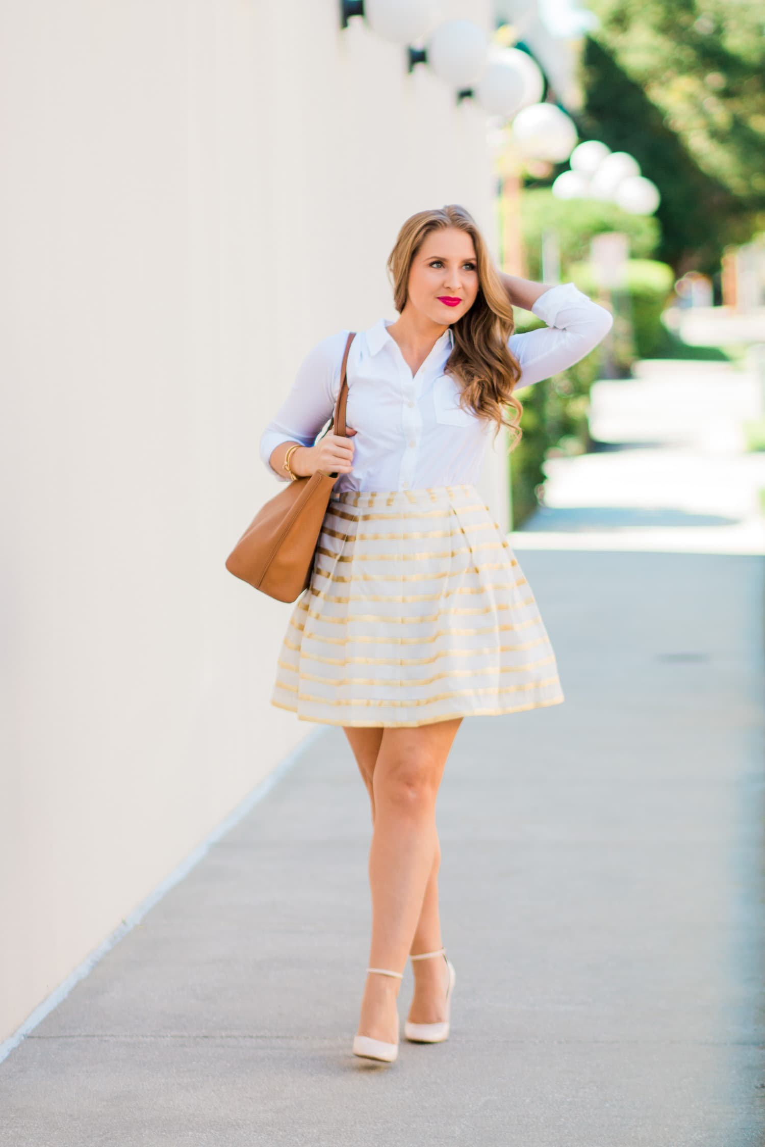 A preppy outfit idea featuring Lilly Pulitzer Kylie skirt in gold and white stripes, Abercrombie classic white button-down Oxford shirt, Charlotte Tilbury The Queen lipstick, Kate Spade clear stud earrings, Tory Burch Perry Tote in cognac, Banana Republic nude pink block heel pumps, Kate Spade pave bow bangle bracelet, and Taudrey engraved gold bracelet styled by fashion blogger Ashley Brooke Nicholas in Orlando, Florida
