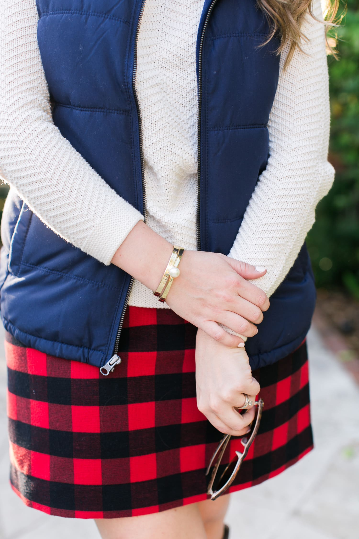 A cozy fall outfit + the best Gap and Old Navy Black Friday Deals +  get $20 back with any $50 purchase at Gap Inc with your Marriott Rewards Premier Card. Preppy fall outfit idea featuring Old Navy navy puffer vest, cream sweater, red plaid skirt, Adia Kibur gold pearl bracelet, an a Mudpie gold engraved Make Your Luck bracelet styled by Florida fashion blogger Ashley Brooke Nicholas