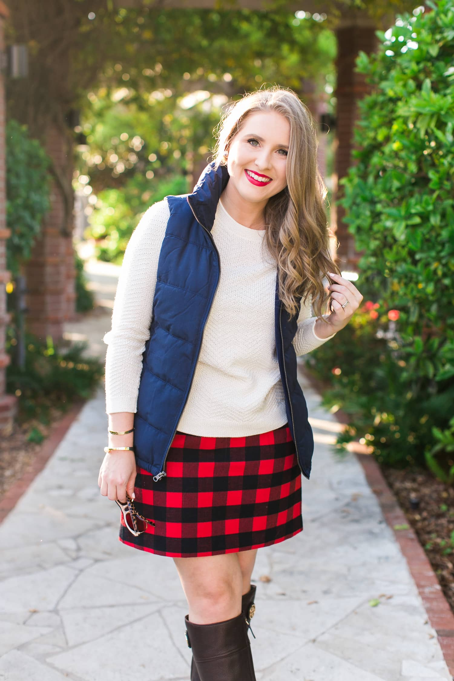 A cozy fall outfit + the best Gap and Old Navy Black Friday Deals +  get $20 back with any $50 purchase at Gap Inc with your Marriott Rewards Premier Card. Preppy fall outfit idea featuring Old Navy navy puffer vest, cream sweater, red plaid skirt, Tory Burch boots, Foster Grant sunglasses, and Clinique Cherry Pop lipstick styled by Florida fashion blogger Ashley Brooke Nicholas