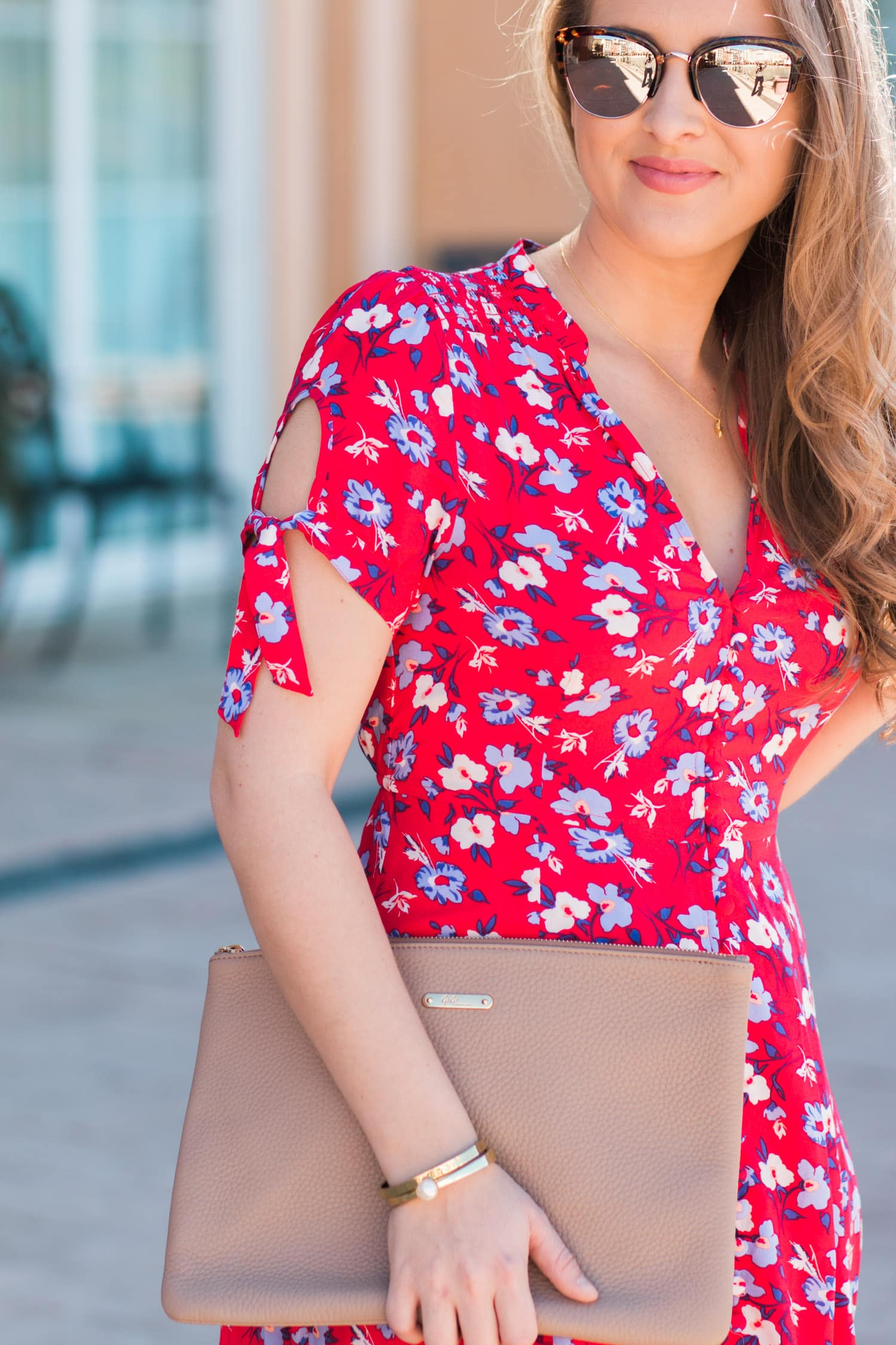 Sunglasses smiling woman and nude purse with red floral dress