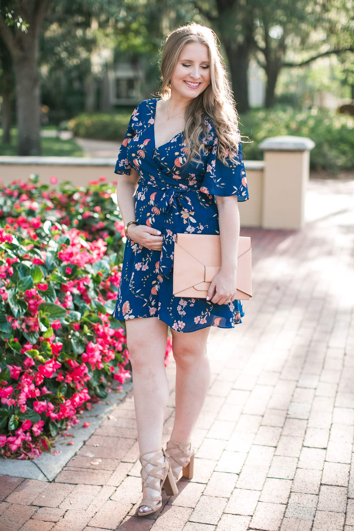 Affordable and maternity-friendly floral wrap dress under $100 styled by Florida fashion and personal style blogger Ashley Brooke Nicholas | BB Dakota Laselle Cherry Blossom Printed Wrap Dress | Maternity Style, maternity fashion, mommy to be, bump style, bump friendly outfits, maternity outfit idea, Sam Edelman Yardley Heeled Sandals, Banana Republic Bow Clutch, nude lace-up sandals, affordable outfit ideas, preppy fashion, preppy style