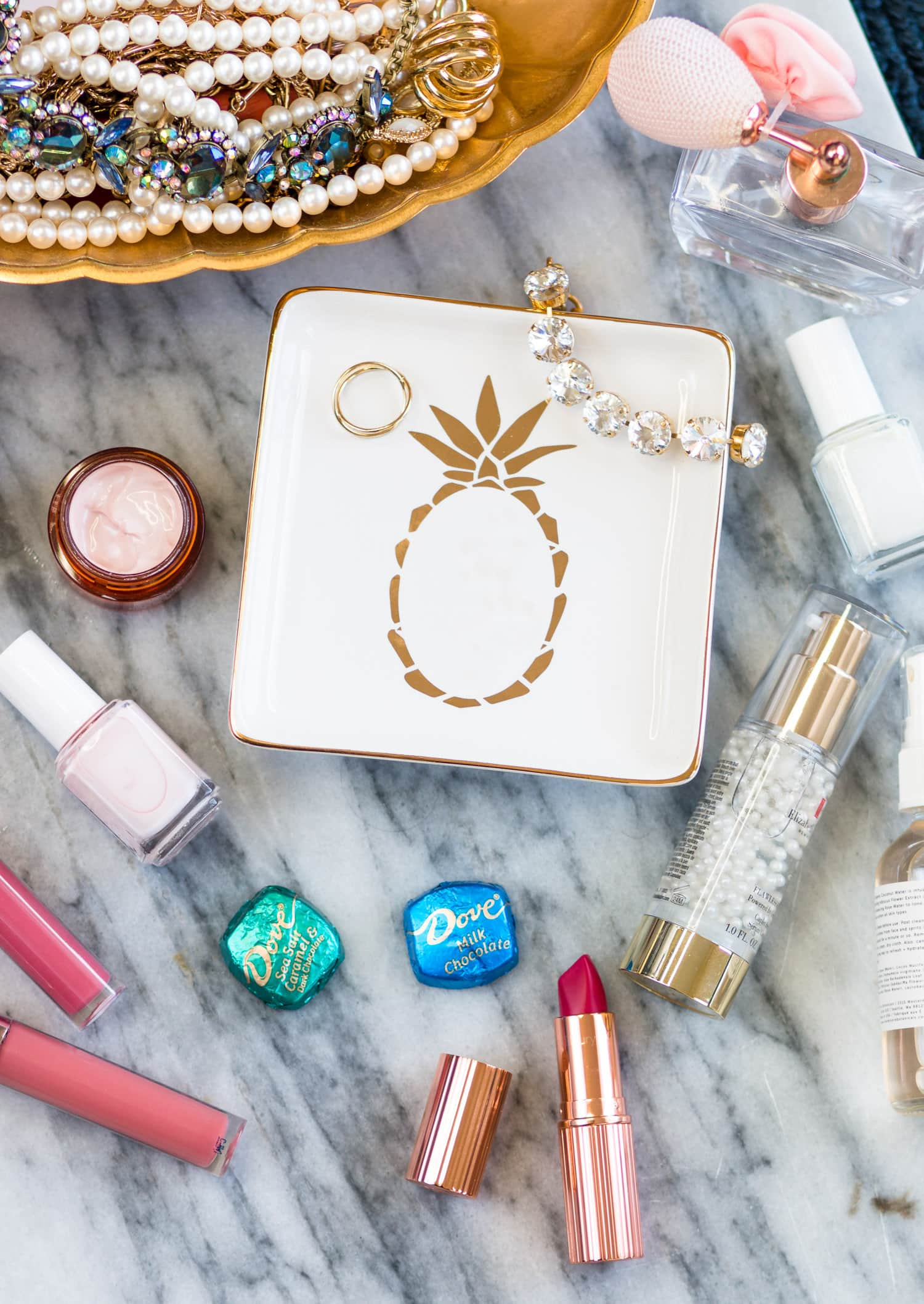 White and gold pineapple trinket dish, sparkly jewelry, feminine perfume, Charlotte Tilbury The Queen lipstick, Dove chocolate | 10 easy ways to de-stress after a long day - including a pamper session with your favorite beauty products and creating a gratitude journal! #unwindwithdove sponsored by @DOVEChocolateUS     | Dove chocolate, stress relief, how to relieve stress, how to calm down, gold candle, stress relief tips, pineapple plate, white and gold, white and gold pineapple, rhinestone bracelet, beautiful jewelry, beautiful flatlay, flatlay, red lipstick, magenta lipstick, white pink nail polish, girly inspiration | Florida lifestyle blogger Ashley Brooke Nicholas