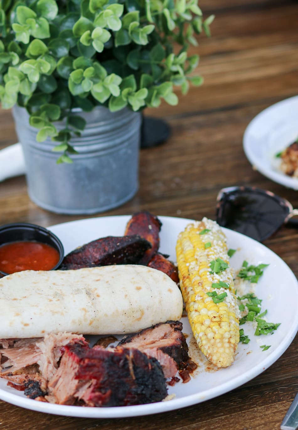 Barbeque and grilled corn at Pig Floyd's | Planning a trip to Orlando? I've rounded up the top 10 things to do in Orlando, Florida, that are guaranteed to make your trip a success. Whether you're moving to Orlando or just headed in on vacation, you will LOVE this list of fun activities in Orlando by Florida travel blogger Ashley Brooke Nicholas #CORTatHome sponsored by   @cortfurniture    affordable travel tips, orlando vacation tips, vacation tips, orlando eye, leu gardens, universal studios, islands of adventure, disney, disney springs