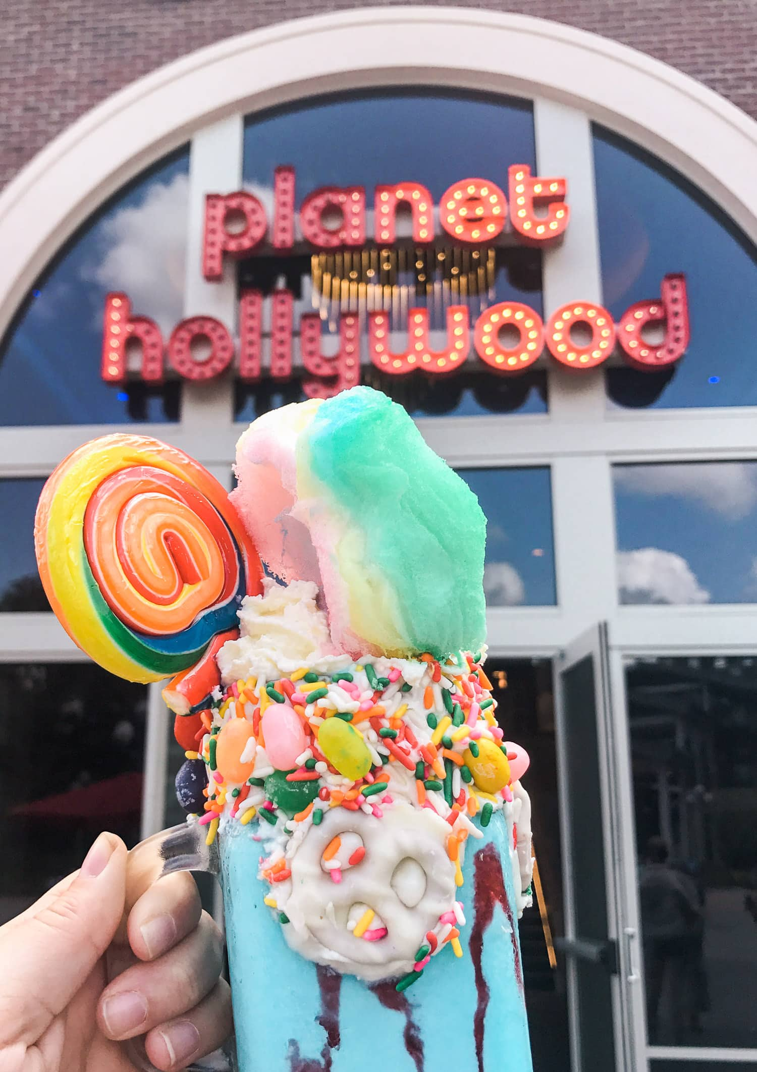 Crazy milkshake with cotton candy and lollipops at Planet Hollywood in Disney Springs | Disney Springs is one of my all-time favorite places to go in Orlando! Planning a trip to Orlando? I've rounded up the top 10 things to do in Orlando, Florida, that are guaranteed to make your trip a success. Whether you're moving to Orlando or just headed in on vacation, you will LOVE this list of fun activities in Orlando by Florida travel blogger Ashley Brooke Nicholas #CORTatHome sponsored by CORT Furniture | affordable travel tips, orlando vacation tips, vacation tips, disney vacation, walt