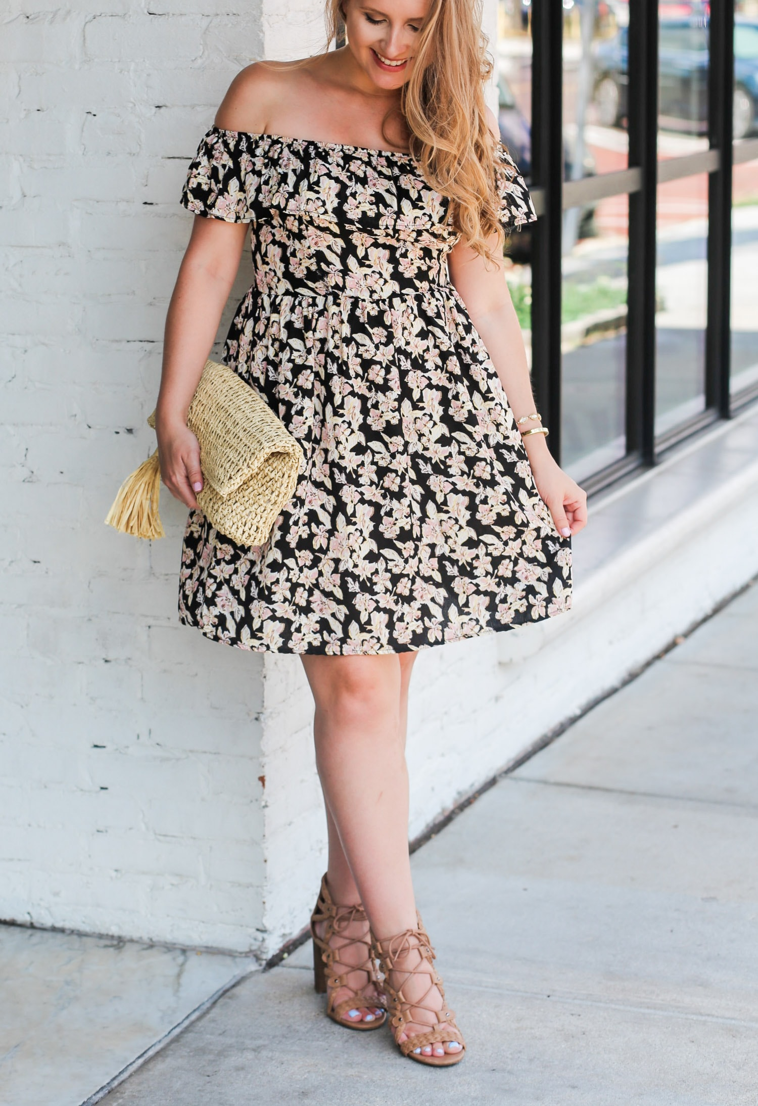 Loving this affordable floral dress for summer! Can you believe this fit and flare sun dress is under $25, AND these gorgeous nude gladiator heeled sandals are also under $25? Click through this pin to see this cute summer outfit idea styled by Orlando, Florida fashion blogger Ashley Brooke Nicholas! | Floral off the shoulder dress, straw clutch with tassel, raffia clutch, lace up sandals, lace up heels, cute summer heels, affordable outfit ideas, fashion blogger outfits, feminine style