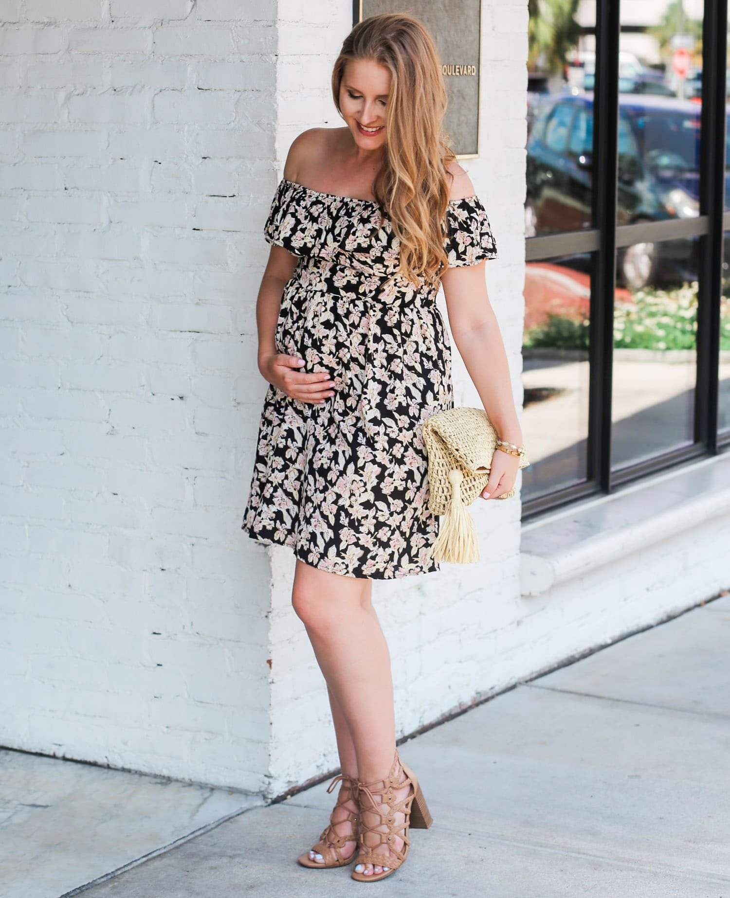 Loving this affordable floral dress for summer! It's non-maternity but still bump friendly! Can you believe this fit and flare sun dress is under $25, AND these gorgeous nude gladiator heeled sandals are also under $25? Click through this pin to see this cute summer maternity outfit idea styled by Orlando, Florida fashion blogger Ashley Brooke Nicholas! | Floral off the shoulder dress, straw clutch with tassel, raffia clutch, lace up sandals, lace up heels, cute summer heels, affordable outfit i