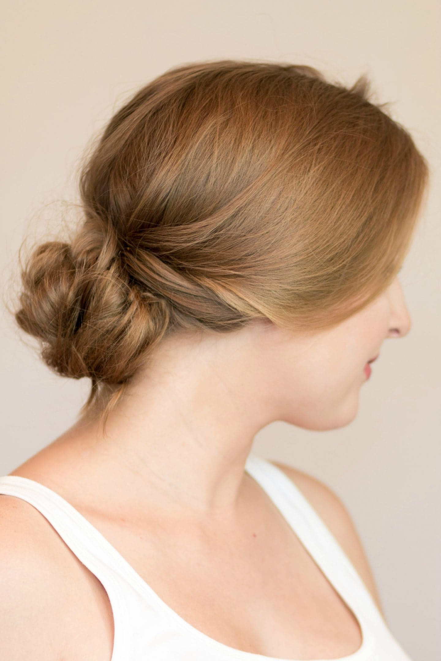 Easy messy braided bun hair tutorial | 4 Easy heatless hairstyles for long hair that don't require hair styling skills or braiding! Learn how to create a faux braided ponytail, messy faux fishtail braid, twisted half-up, and messy braided bun in these easy hair tutorial by Orlando, Florida beauty blogger Ashley Brooke Nicholas! #MyHCLook sponsored by Hair Cuttery | easy hairstyles, no-heat hairstyle, faux braids, faux braid tutorial, how to braid your hair, messy bun, fishtail braid, long dirty blonde hair