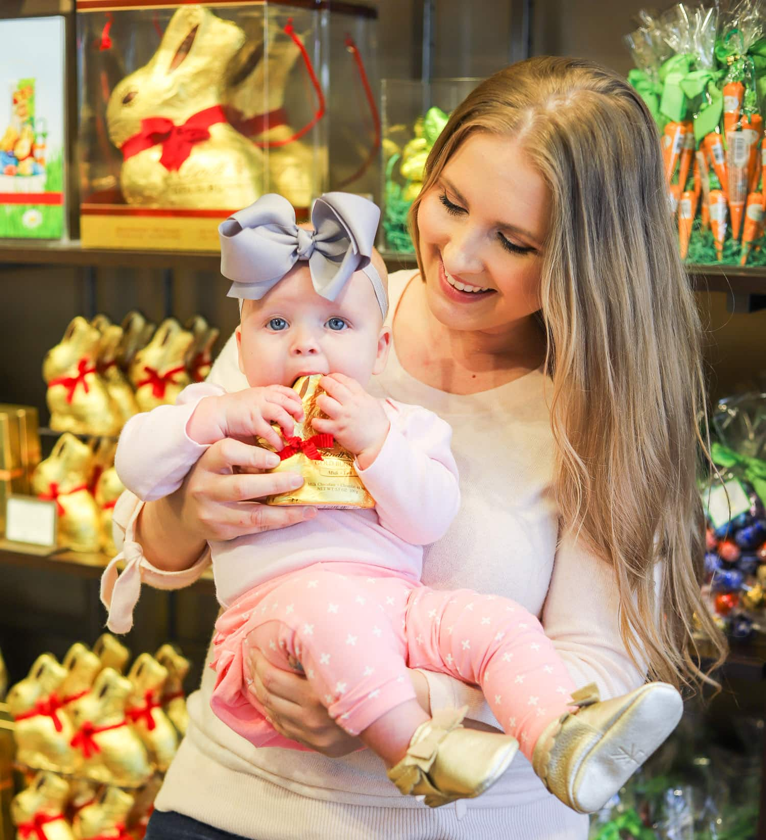 cute baby girl eating lindt chocolate gold bunny mom smiling at lindt store